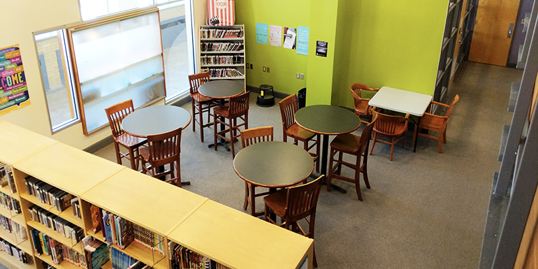 Image of the teen department of Cornwall Public Library including lime green walls, circular tables, book stacks, and various chairs